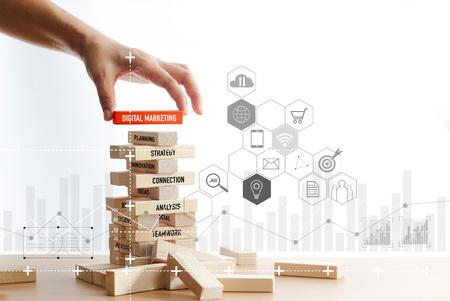 Main tenant un bloc de bois avec mot de marketing numérique avec connexion réseau numérique icône sur fond blanc de structure de blocs de bois. Concept de marketing numérique.