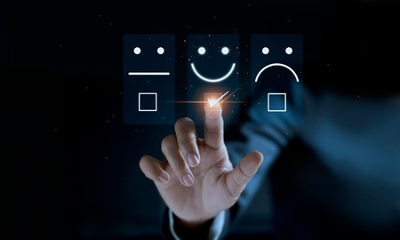 Finger of businessman touching and check mark icon face emoticon smile on dark background, service mind, service rating. Satisfaction and customer service concept Reklamní fotografie