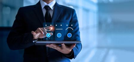Geschäftsmann, der Gesicht Emoticon Lächeln auf dem Tablet berührt und zeichnet, Service-Geist. Blauer Hintergrund. Kundenservice-Konzept. Standard-Bild