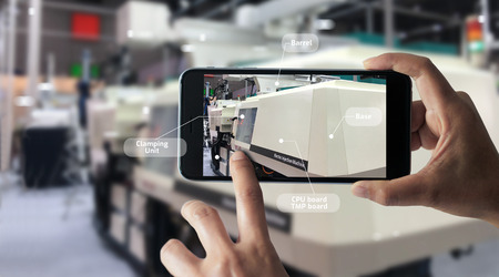 Augmented reality concept. AR. Industrial 4.0 , Hand of engineer holding mobile smart phone using virtual AR to check the work of electric machine on smart factory background. Stockfoto