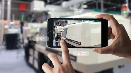 Concepto de realidad aumentada. ARKANSAS. Industrial 4.0, mano de ingeniero sosteniendo un teléfono inteligente móvil usando AR virtual para verificar el trabajo de la máquina eléctrica en el fondo de la fábrica inteligente.