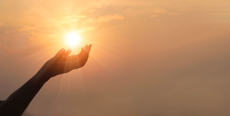 Woman hands praying for blessing from god on sunset background Standard-Bild