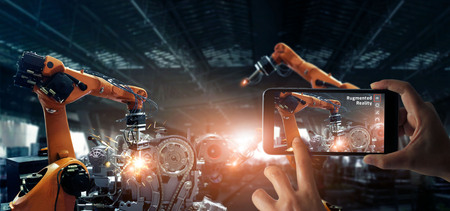 Augmented reality industry concept. Hand holding mobile smartphone use AR application to check and control welding robotics automatic arms machine in intelligent factory automotive industrial with monitoring system software. Digital manufacturing operation. Industry 4.0
