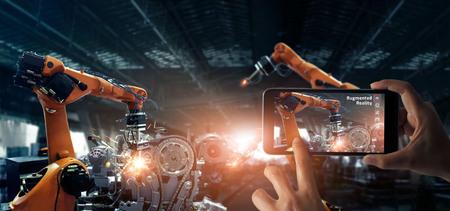 Industriekonzept der erweiterten Realität. Hand, die ein mobiles Smartphone hält, verwendet eine AR-Anwendung, um automatische Schweißroboter in der intelligenten Automobilindustrie mit Überwachungssystemsoftware zu überprüfen und zu steuern Digitaler Fertigungsbetrieb. Industrie 4.0