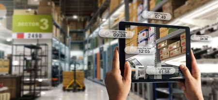 Augmented-Reality-Online-Shopping-Konzept. E-Commerce und digitales Marketing. Hand, die ein digitales Tablet-Smartphone hält, verwendet die AR-Anwendung, um die Kommissionierzeit auf dem Hintergrund der Lagerfabrik zu überprüfen.