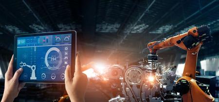 Ingeniero que verifica y controla la máquina de brazos automáticos de robótica de soldadura en una fábrica inteligente industrial automotriz con software de sistema de monitoreo. Operación de fabricación digital. Industria 4.0
