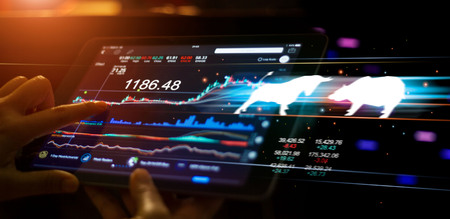 A businessman using a tablet mobile device to check and analyzing market data with bull and bear shapes symbols of stock market trends on them, stock market exchange on interface virtual screen.