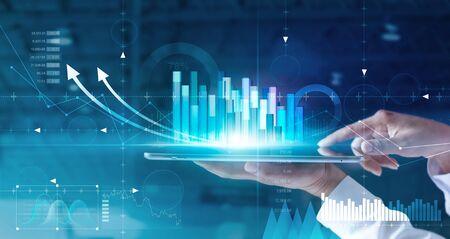 Handen van zakenman die verkoopgegevens en economische groeigrafiek op tablet en hologramscherm analyseren. Stockfoto