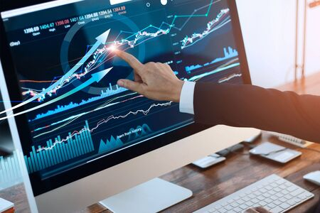 Hand of businessman touching graph and chart stock market on screen in work place.