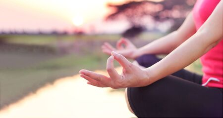 Woman practices yoga and meditates on the nature sunset