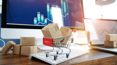 Paper boxes in shopping cart and credit card on keyboard and sales data economic growth graph on computer  screen Imagens