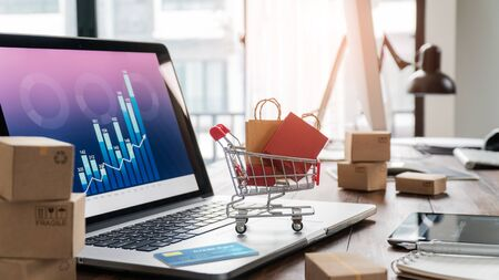 Shopping bags in shopping cart and credit card on laptop with paper boxes on table and sales data economic growth graph on screen