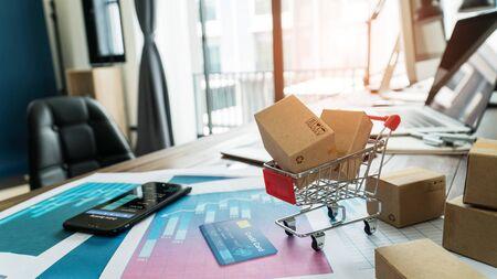 E-commerce. Papieren dozen in winkelwagen en creditcard met smartphone op grafiek van de economische groei van verkoopgegevens Stockfoto