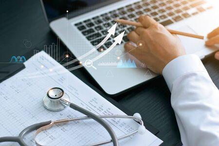 Gesundheitswesen-Geschäftsdiagramm und medizinische Untersuchung und Geschäftsmann, der Daten- und Wachstumsdiagramm auf Laptop analysiert