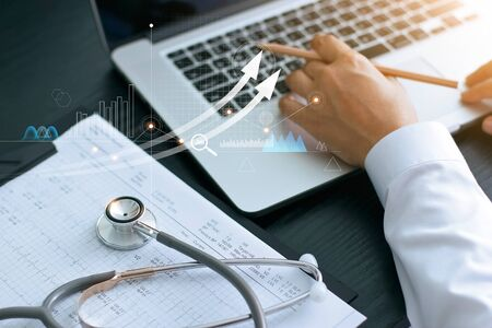 Healthcare business graph and Medical examination and businessman analyzing data and growth chart on laptop