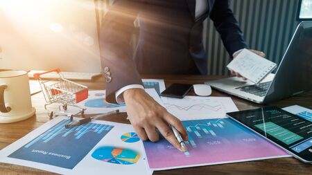 Businessman analyzing sales data and economic growth and pointing at business report document with graph chart financial diagram