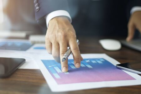 Businessman hand pointing at graph chart growth business document