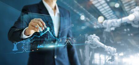 Ingeniero gerente que analiza y controla la automatización de la máquina de brazos de robot en el software de la moderna interfaz virtual de datos en tiempo real en una fábrica inteligente de operaciones de fabricación industrial y digital.