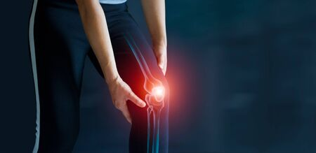 Deporte mujer que sufre de dolor en la rodilla. Problemas de tendones e inflamación de las articulaciones sobre fondo oscuro. Asistencia sanitaria y médica.