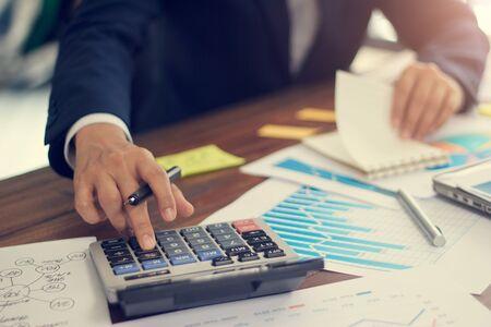 Uomo d'affari che utilizza la calcolatrice per calcolare il budget e analizzare i dati di vendita e il grafico di crescita, pagamenti, finanziamento aziendale e contabilità bancaria. Archivio Fotografico