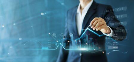 De zakenman trekt de groeigrafiek en de vooruitgang van zaken en analyseert financiële en investeringsgegevens, bedrijfsplanning en strategie op blauwe achtergrond.