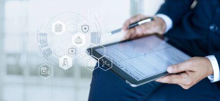 Krankenversicherungskonzept, Geschäftsmann, der ein medizinisches Antragsformular mit Versicherungssymbol Gesundheitsversorgung auf Tablet digital ausfüllt.