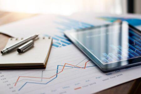 Raport dokumentu biznesowego na papierze i tablecie z danymi sprzedaży i wykresem wzrostu firmy finansowej na tle tabeli.