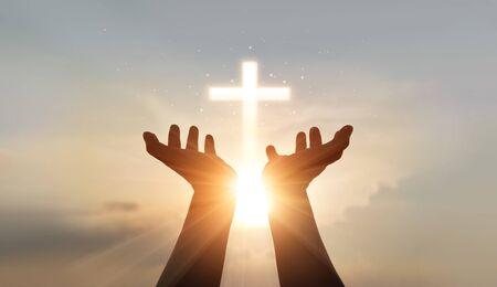 El hombre manos palma hacia arriba rezando y adorando a la cruz, la terapia eucarística bendice la ayuda de Dios, la esperanza y la fe, el concepto de religión cristiana en el fondo del atardecer.