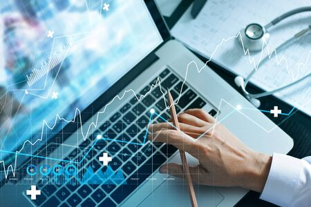 Analyzing data and growth chart healthcare business graph  and medical examination on laptop screen. Stock Photo