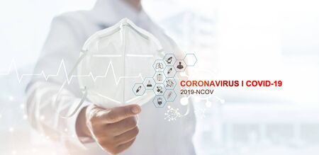 Doctor holding a mask to prevent Coronavirus or Covid-19 for the Inhibition of disease outbreaks of rapidly spreading and icon medical healthcare on hospital background. 写真素材