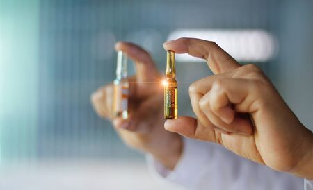 A scientist holding and analysis bottles with Coronavirus or Covid-19 vaccine for the Inhibition of disease outbreaks of rapidly spreading, Healthcare and medicine, 2019-NCOV.