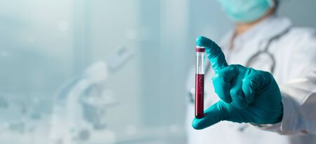 Doctor holding test glass tube with blood for covid-19 analyzing on laboratory