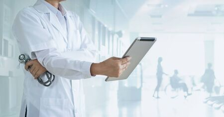 Cardiologist doctor with stethoscope analyzing patient data on tablet in hospital Stockfoto