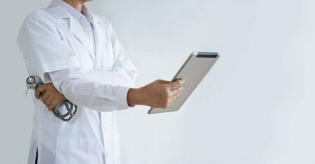 Doctor with stethoscope in hand using a digital tablet on white 版權商用圖片