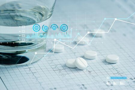 Health care and Medical, Patients' pills and water glass placed on a heartbeat report paper And a graph of the growth of medical and healthcare businesses.