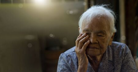 An elderly Asian woman with Alzheimer's and memory loss sitting alone in house 版權商用圖片