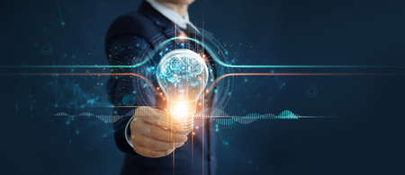 Businessman holding illuminated light bulb with brain inside, idea, creativity, innovation and inspiration of business on network connection background.