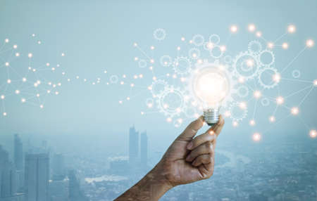 Double exposure. New ideas. Innovation and creativity. Technology and development. Businessman hand holding light bulb and cog wheel on city background. Blue tone. 版權商用圖片 - 161884022