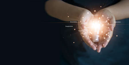 Abstract, Hands holding a light bulb of network, innovation, creativity and inspiration on dark background.
