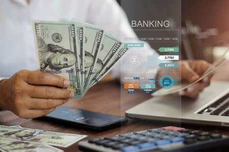 Banking and finance accounting, Businessman holding banknote and analyzing data growth graph on mobile and laptop and using calculator to calculate the numbers currency exchange. 版權商用圖片 - 161884032