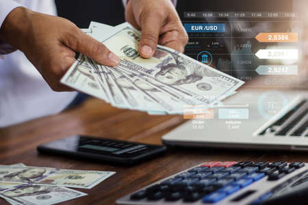 Banking and finance accounting, Businessman holding banknote and analyzing data growth graph on mobile and laptop and using calculator to calculate the numbers currency exchange. 版權商用圖片