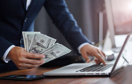 Businessman holding banknote and using laptop analyzing calculate the numbers currency exchange on global network,  Investment, Banking and financial. 版權商用圖片