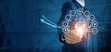 Businessman holding light bulb and analyzing sales data and economic growth graph. Technology and icon customer global network connection. New idea. creativity and inspiration. digital marketing.