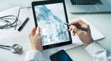 Doctor draw healthcare business graph data and growth. Medical examination and doctor analyzing medical report network connection on tablet screen in hospital. 版權商用圖片