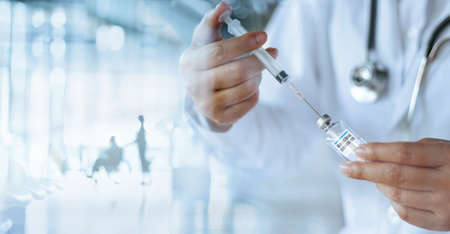 Doctor hold syringe and vial containing covid-19 coronavirus vaccine ready for injection. Laboratory accelerating develop vaccine and medicine for covid-19 pandemic. Healthcare and medical technology. 版權商用圖片