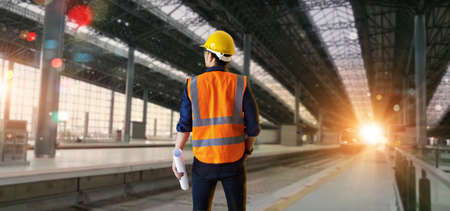 Back view of Manager industrial engineer standing and holding a blueprints and checking structure and of construction railway site of high speed background. Technology and engineering. transportation and logistics. 版權商用圖片
