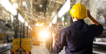 Factory engineer hold tablet manage inventory control and deliverly smart transportation through intelligent warehouse management system.Global logistic contribution and industrial innovative. 版權商用圖片 - 161884129