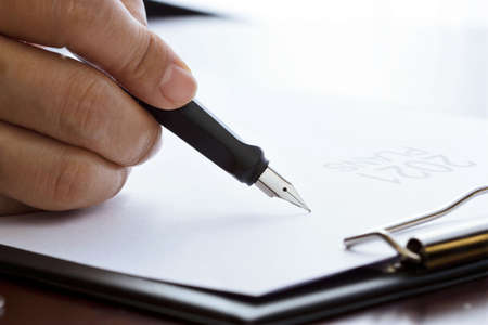 Hand of businessman with pen writing business plans 2021 on white paper. 版權商用圖片