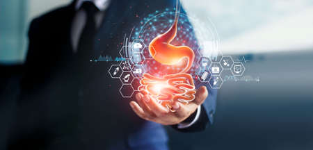 Businessman holding stomach in handand stomach ache from gastritis or GERD (gastroesophageal reflux disease).Digestive disorder causes patient heartburn pain or acid indigestion.Medical   and health insurance.