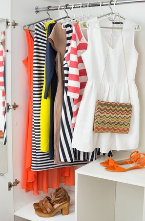 Set of bright colorful female fashion clothes on the hangers for spring and summer wardrobe, handbag, sandals in white cabinet, vertical Foto de archivo